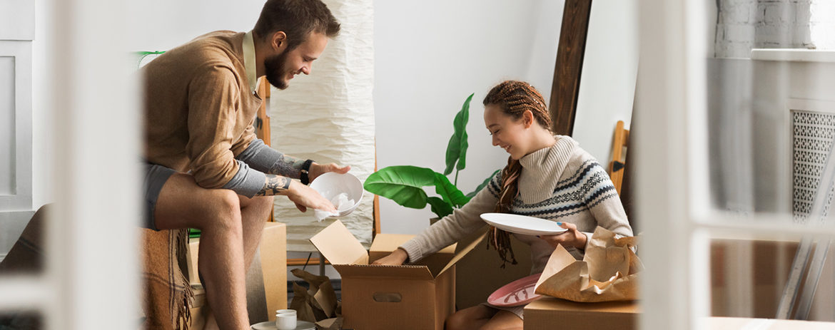 Couple unpacking boxes in home