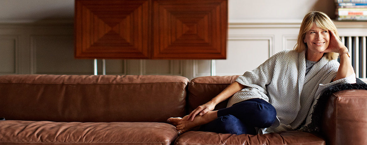 Confident woman on couch in her home