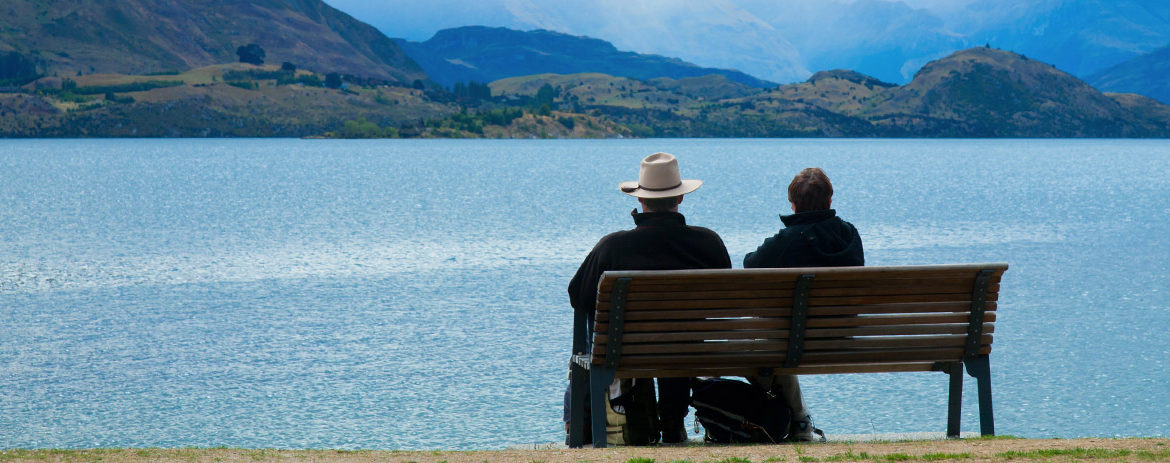 Retired couple sitting on chair looking out at Lake Wanaka