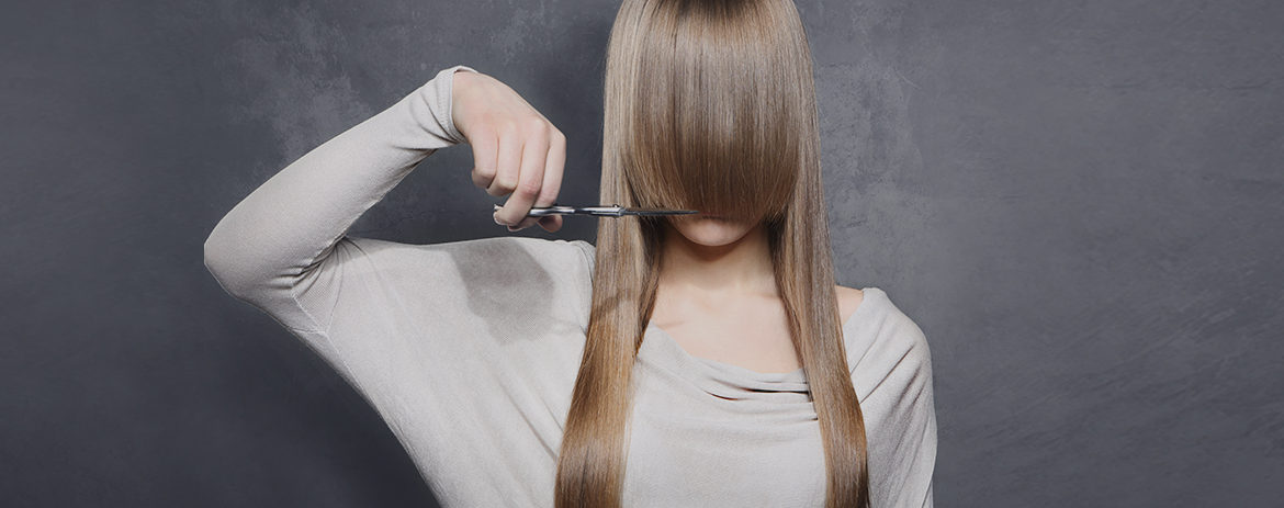 Female cutting her fringe