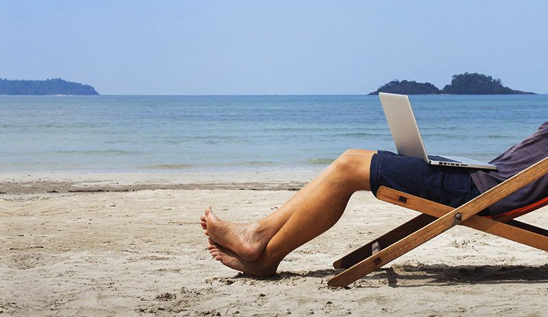 Man sitting on beach reclining with laptop