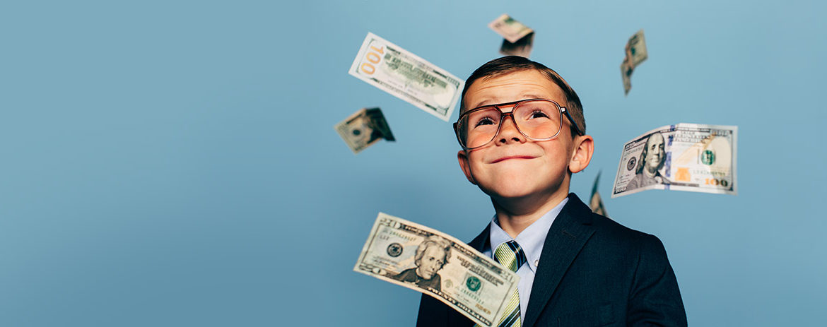 Young boy posing with money drifting around him
